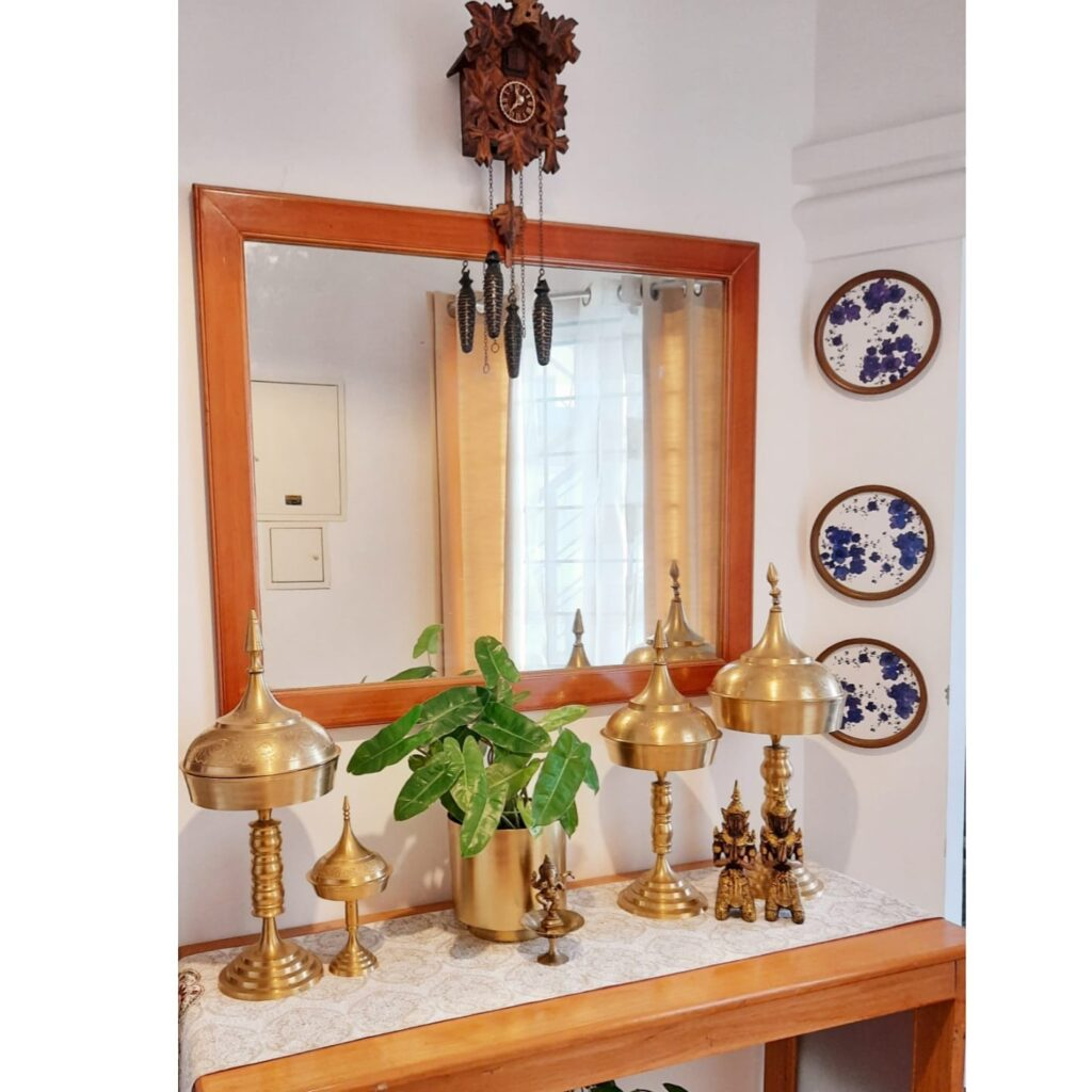A traditional Assamese bell metal piece, green plant, brass collection, wall decor and mirror at the corner of the room | Upasana Talukdar home tour | thekeybunch decor
