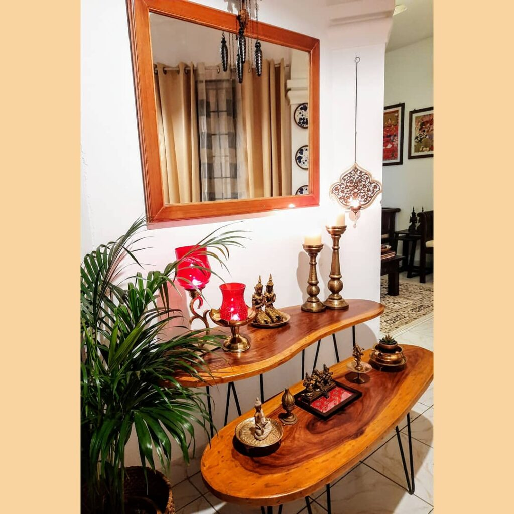 the corner of the room is decorated with brass collection, green plant, mirror view and wooden table | Upasana Talukdar home tour | thekeybunch decor