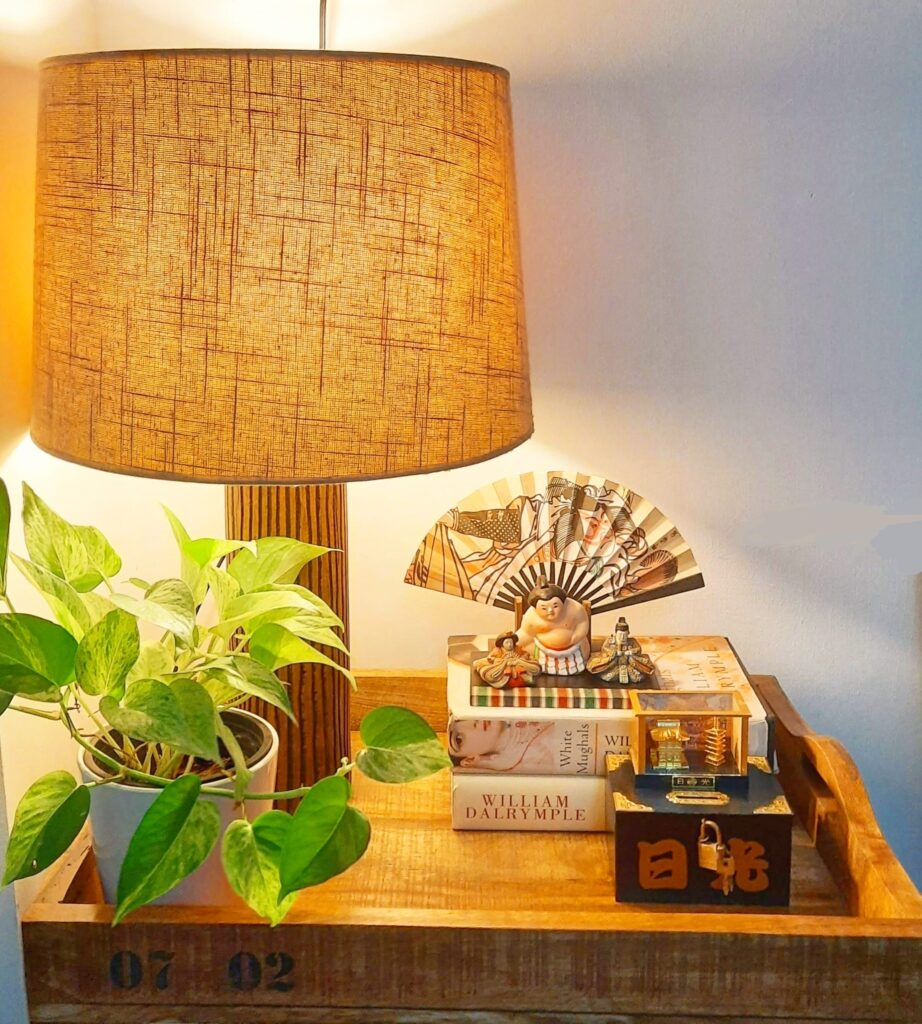 The apartment living room is decorated with beautiful vignette, green plant and table lamp on a wooden tray | Upasana Talukdar home tour | thekeybunch decor