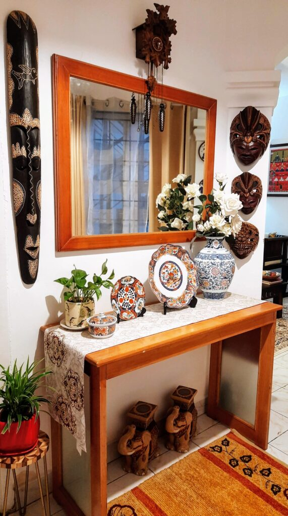 the corner of the room is decorated with a traditional Assamese bell metal piece, wall mask, green plant, decorative plates and a beautiful porcelain vase | Upasana Talukdar home tour | thekeybunch decor