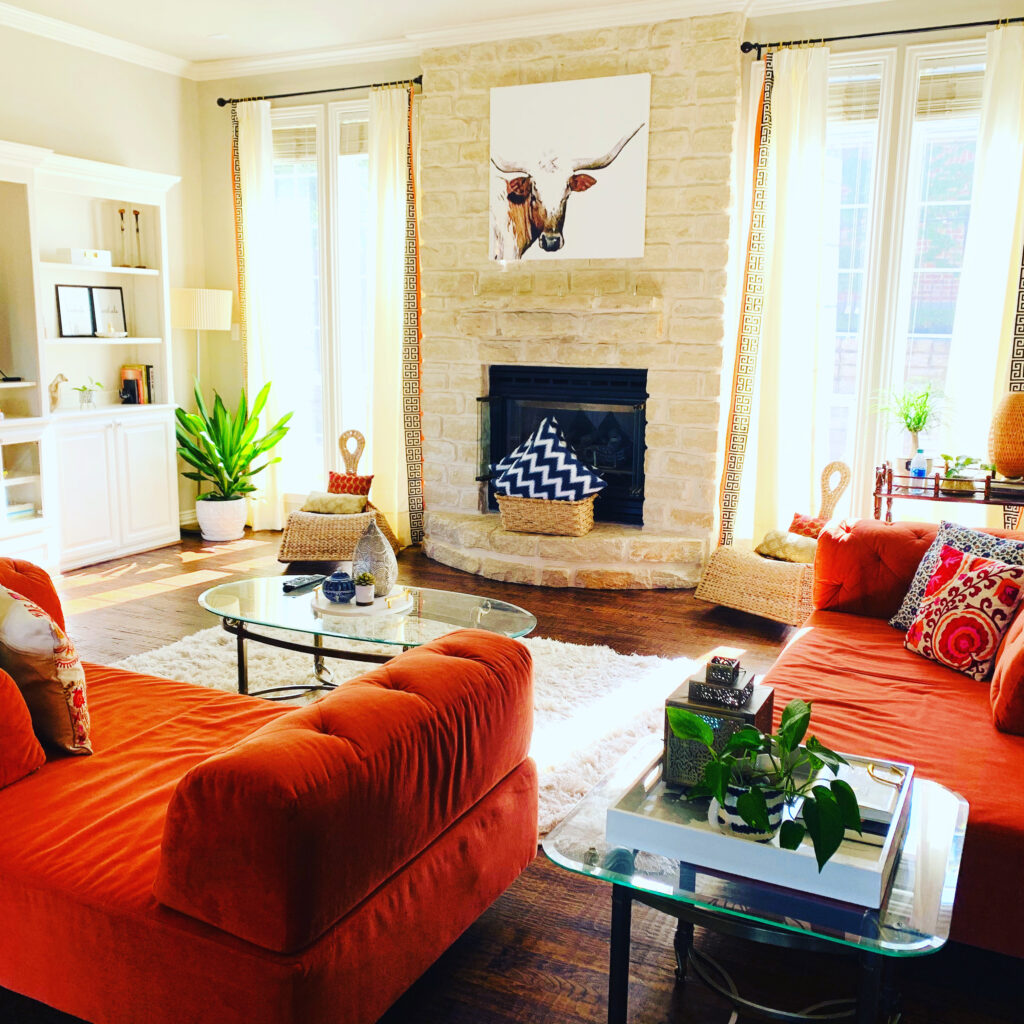 the living room is decorated with orange sofa, green plants and art on the wall | Ruma's Indian Home in Texas | theKeybunch decor blog