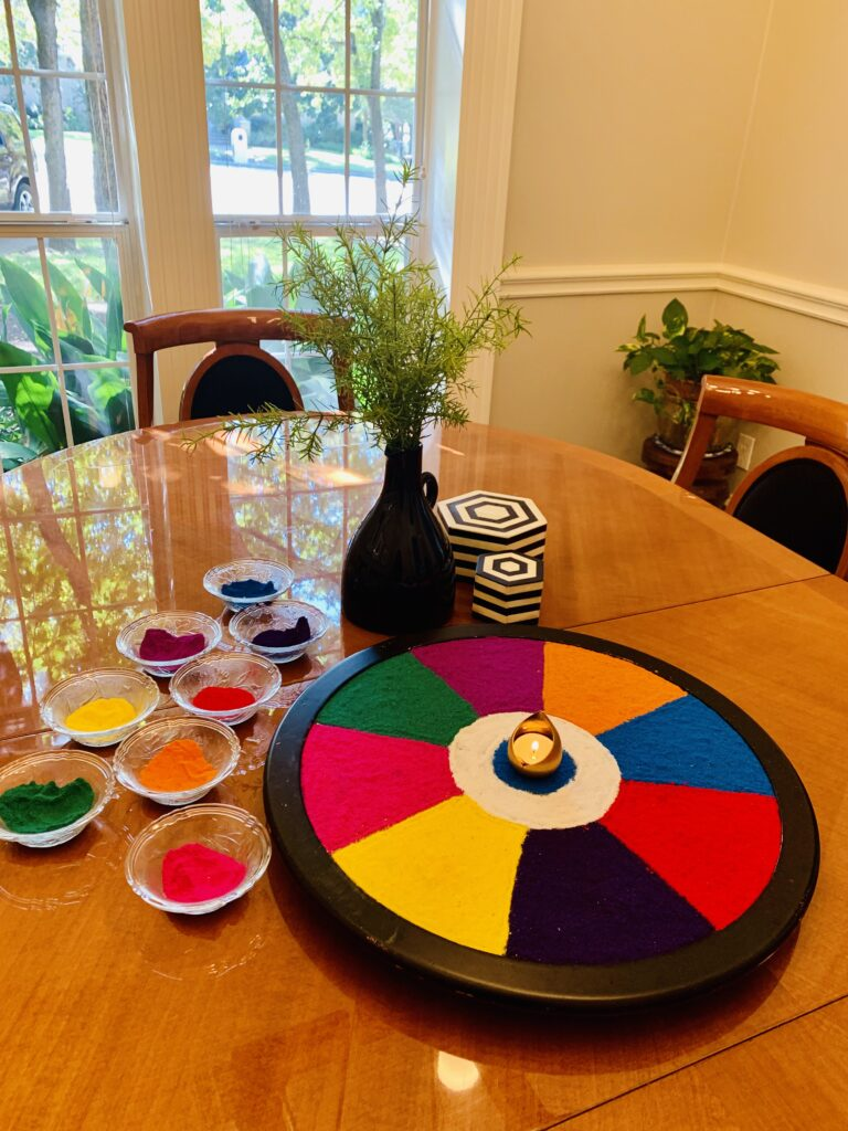 the colorful rangoli, green plants and rangoli powder decorated for Indian festival | Ruma's Indian Home in Texas | theKeybunch decor blog