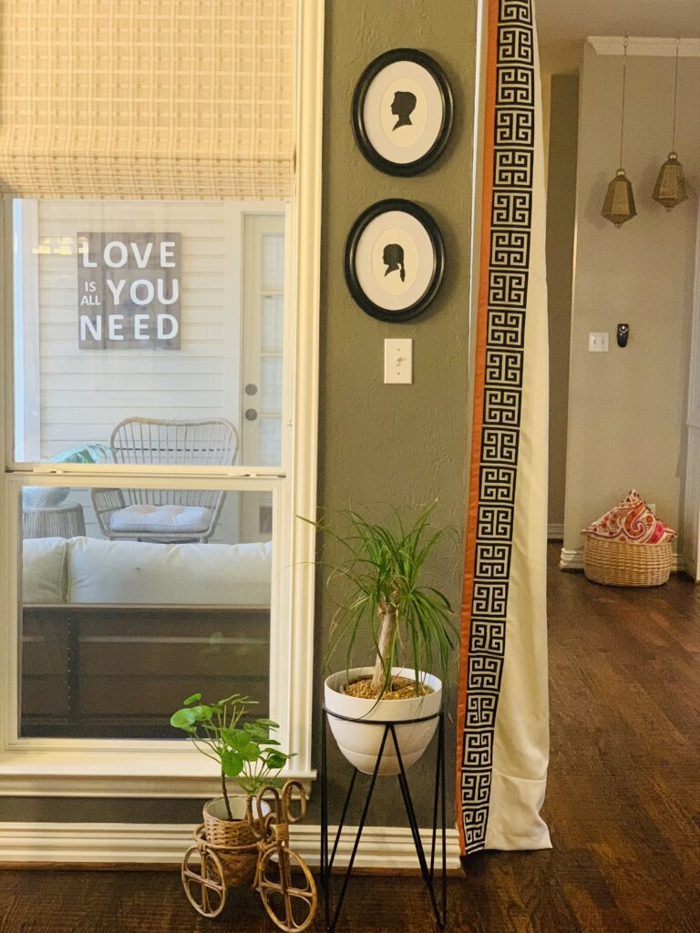 silhouette art, brass bell on the wall and green plants at the corner of the room  | Ruma's Indian Home in Texas | theKeybunch decor blog