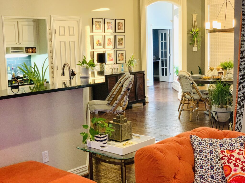 the room is decorated with wall gallery, green plants, vintages and orange chair | Ruma's Indian Home in Texas | theKeybunch decor blog