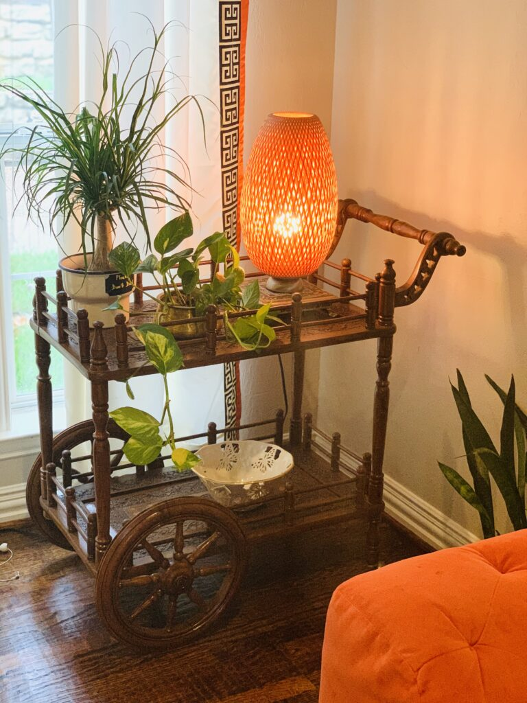 the carved wood tea trolley is decorated with green plants and lamp shade | Ruma's Indian Home in Texas | theKeybunch decor blog