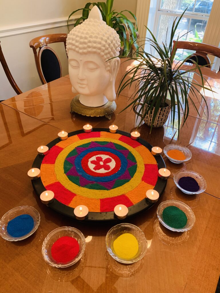 the colorful rangoli, candle glamour, buddha statue and green plants decorated at Indian festival | Ruma's Indian Home in Texas | theKeybunch decor blog