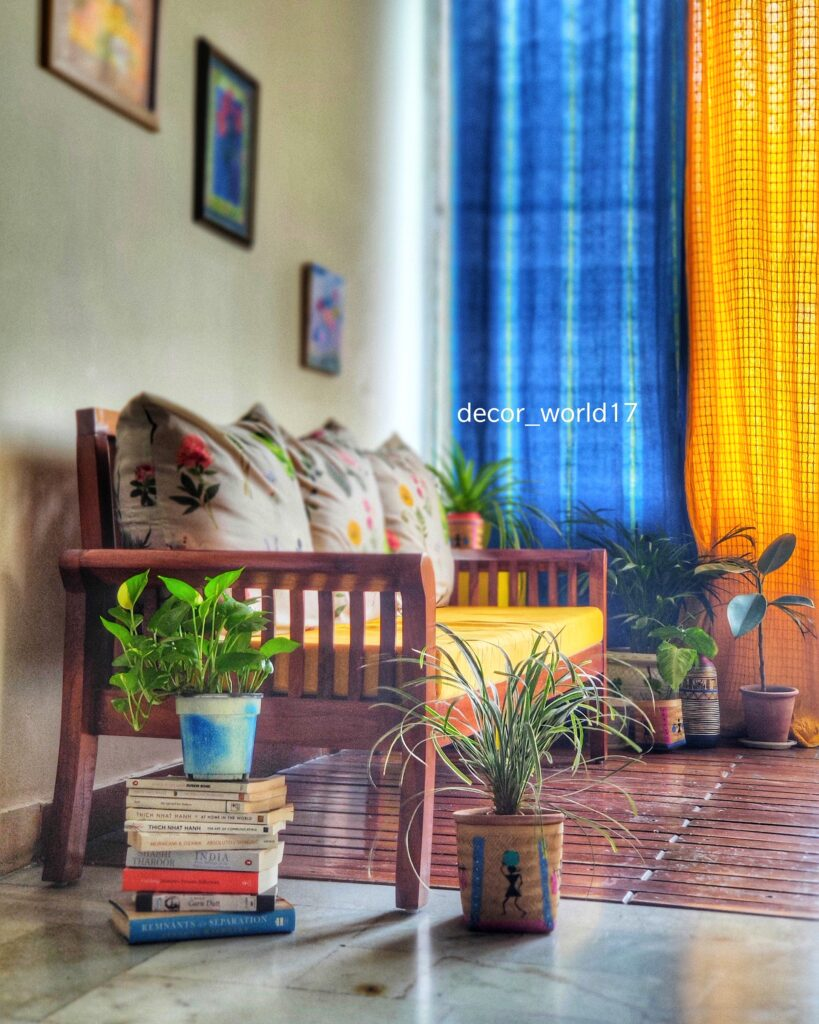 The stack of books, colorful curtains, green plants, wall frames, and antique chair at the corner of the room | Dharitri home tour | thekeybunch decor