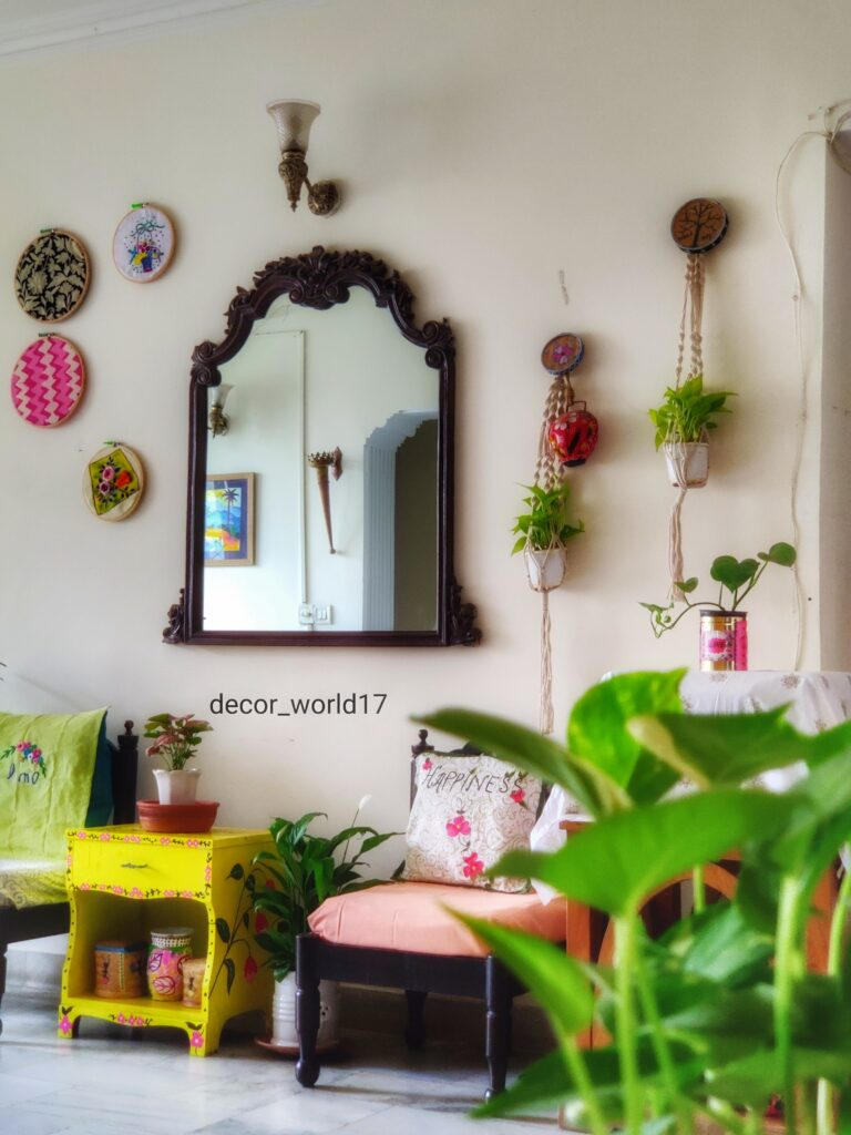 The corner of the room is decorated with antique chairs, yellow table, green plants, decorative mirror and wall decor | Dharitri home tour | thekeybunch decor