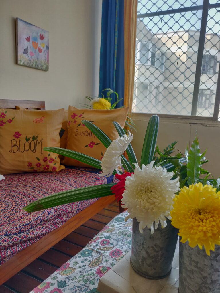 Handpainted cushion covers, art frame and fresh flowers make the room look bright and beautiful | Dharitri home tour | thekeybunch decor