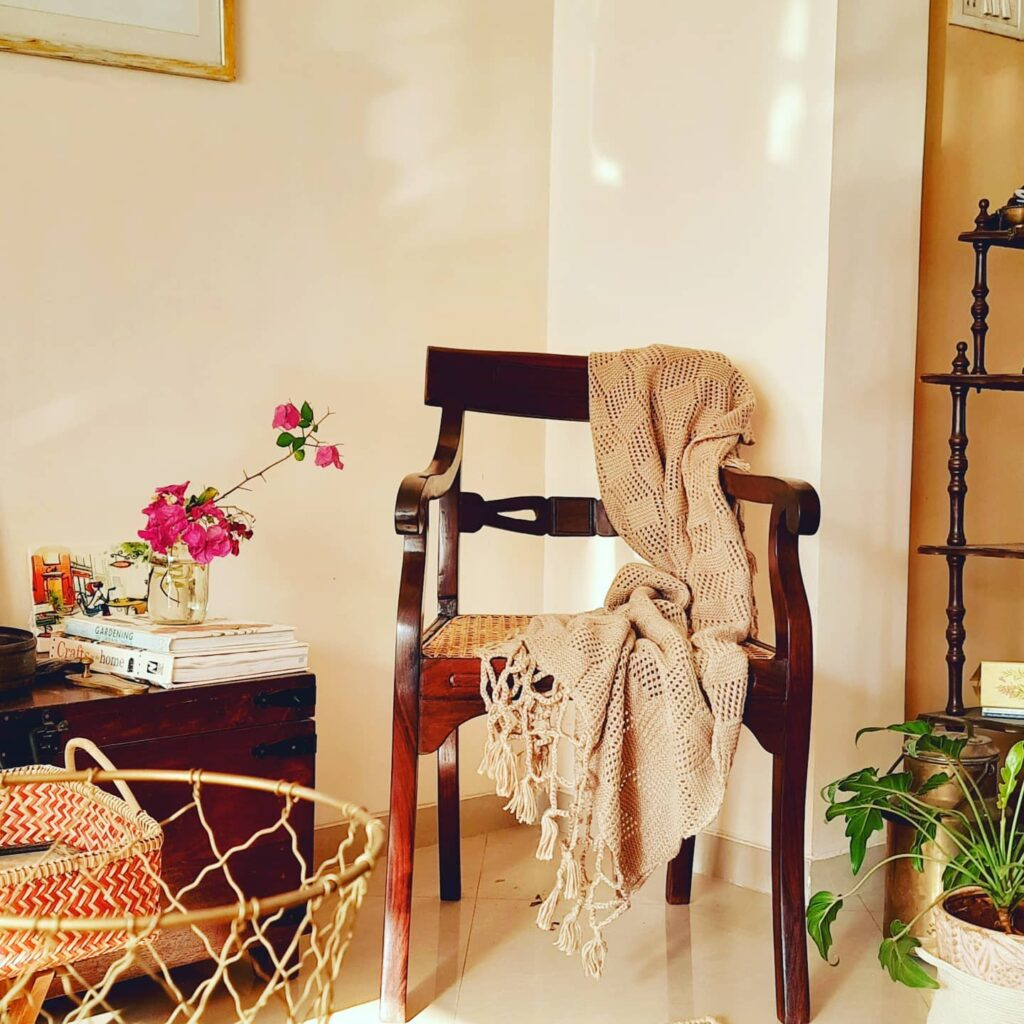 the gorgeous woolen throw, vintage chair, fresh flowers and green plants at the corner of the room - Decor trends 2021 for Indian homes | Thekeybunch decor blog