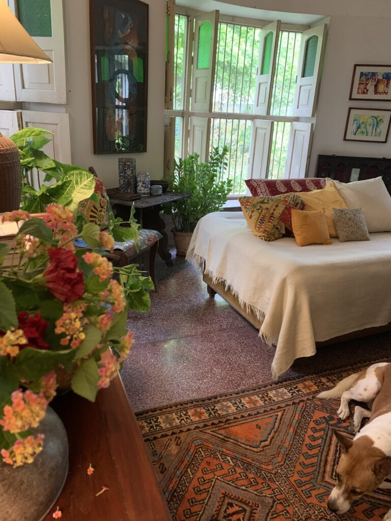 the room is decorated with cushion covers, gallery wall, side table, green plants and fresh flowers - Decor trends 2021 for Indian homes | Thekeybunch decor blog