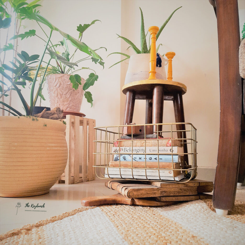 The corner of the room are decorated with green plants, orange candle stands and iron storage basket books | What does an Interior Stylist do | Thekeybunch decor blog