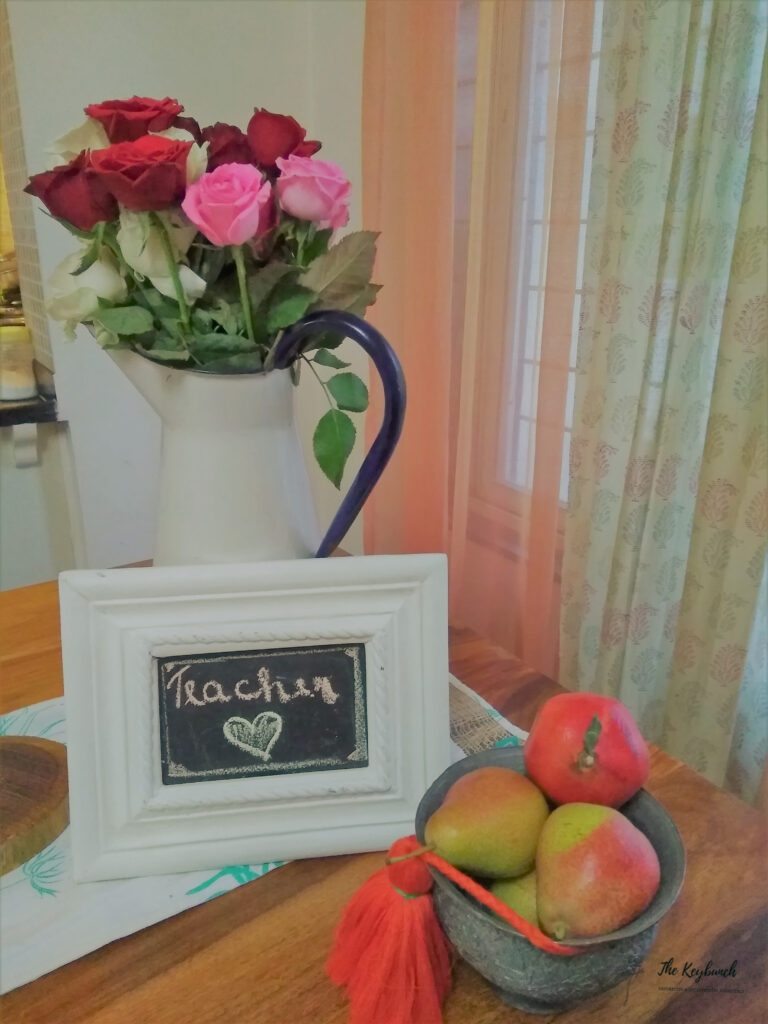 Rose in vintage jug, white frame and some apple fruits on the side table | Areas where an Interior Stylist can help you | Thekeybunch decor blog