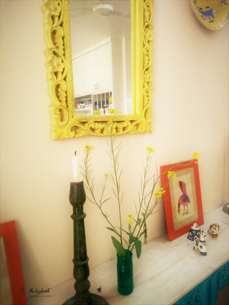 The corner of the room is decorated with yellow mirrored frame, green candle stand, plant and frame | Areas where an Interior Stylist can help you | Thekeybunch decor blog