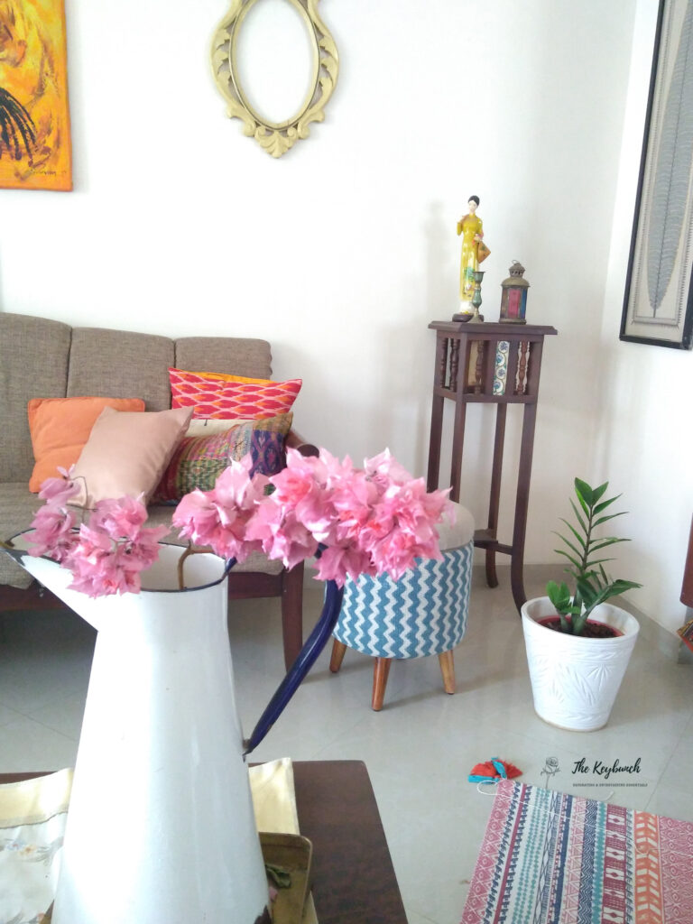 The living room is styling up with colorful cushion cover, zz green plant, bougainvillea flower, ottoman chair and vintage side table | Areas where an Interior Stylist can help you | Thekeybunch decor blog