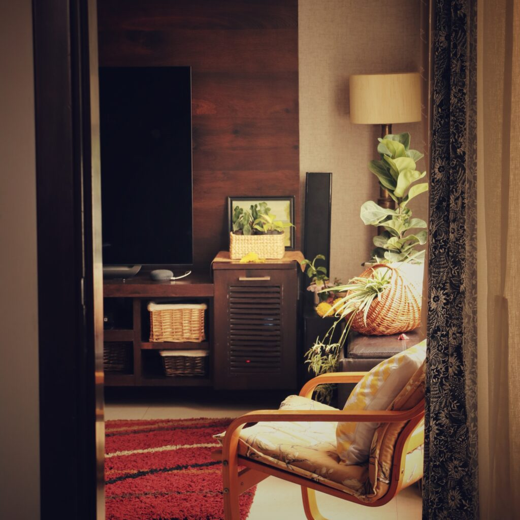 The basket, poang chair and green plant at the corner of the room | Home Tour: A beautiful Antique Modern home in Bangalore