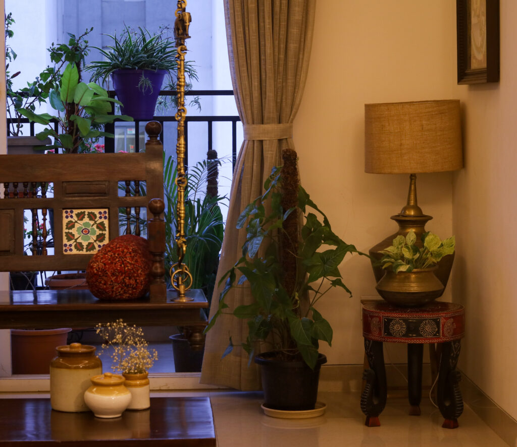 A swing set, green house plants, brass table lamp are decorated in living room | Home Tour: A beautiful Antique Modern home in Bangalore