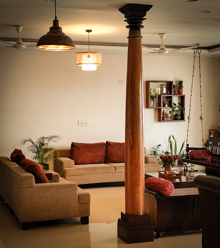 8ft pillars from Tamil Nadu, traditional jhoola swing, and green plants decorated in living room | Home Tour: A beautiful Antique Modern home in Bangalore