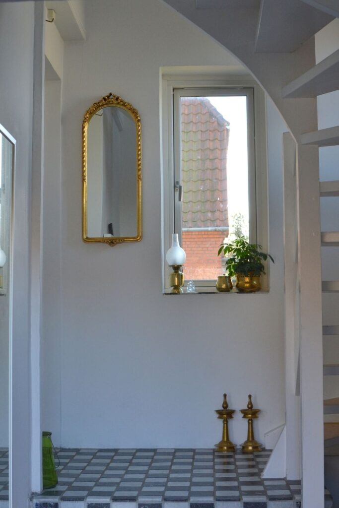 The gold mirror and vintage brass collection at the corner of the room | Naina's Scandi-Minimalist Home with Indian Accents