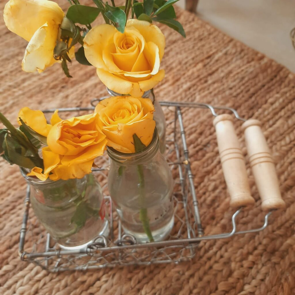 Reused the wire caddy basket as an interesting flower holder, using 4 bottles to hold flowers | A case for Baskets | TheKeybunch decor blog