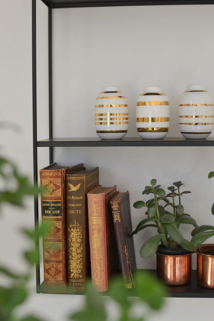 The vintage books, brass planter filled with green plants and miniature vases | Naina's Scandi-Minimalist Home with Indian Accents