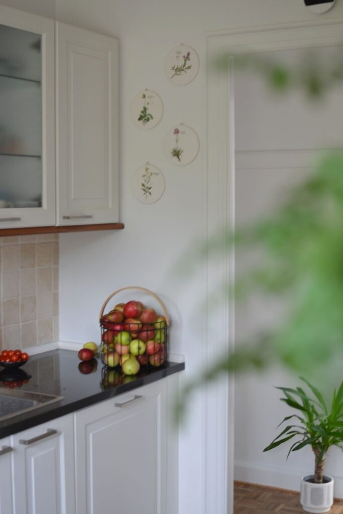 The black metal basket is filled with home grown apples and floral wall plates at the corner of the kitchen | Naina's Scandi-Minimalist Home with Indian Accents
