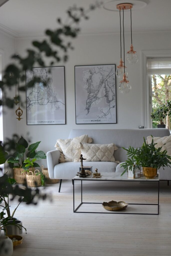 White living room decorated with green plants, hanging lights, wall map frame and basket planter | Naina's Scandi-Minimalist Home with Indian Accents