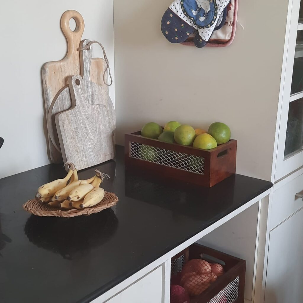 The kitchen filled with a flat woven plate to hold the bananas, handmade chopping or cheese board and baskets filled with fruits and potatoes | A case for Baskets | TheKeybunch decor blog