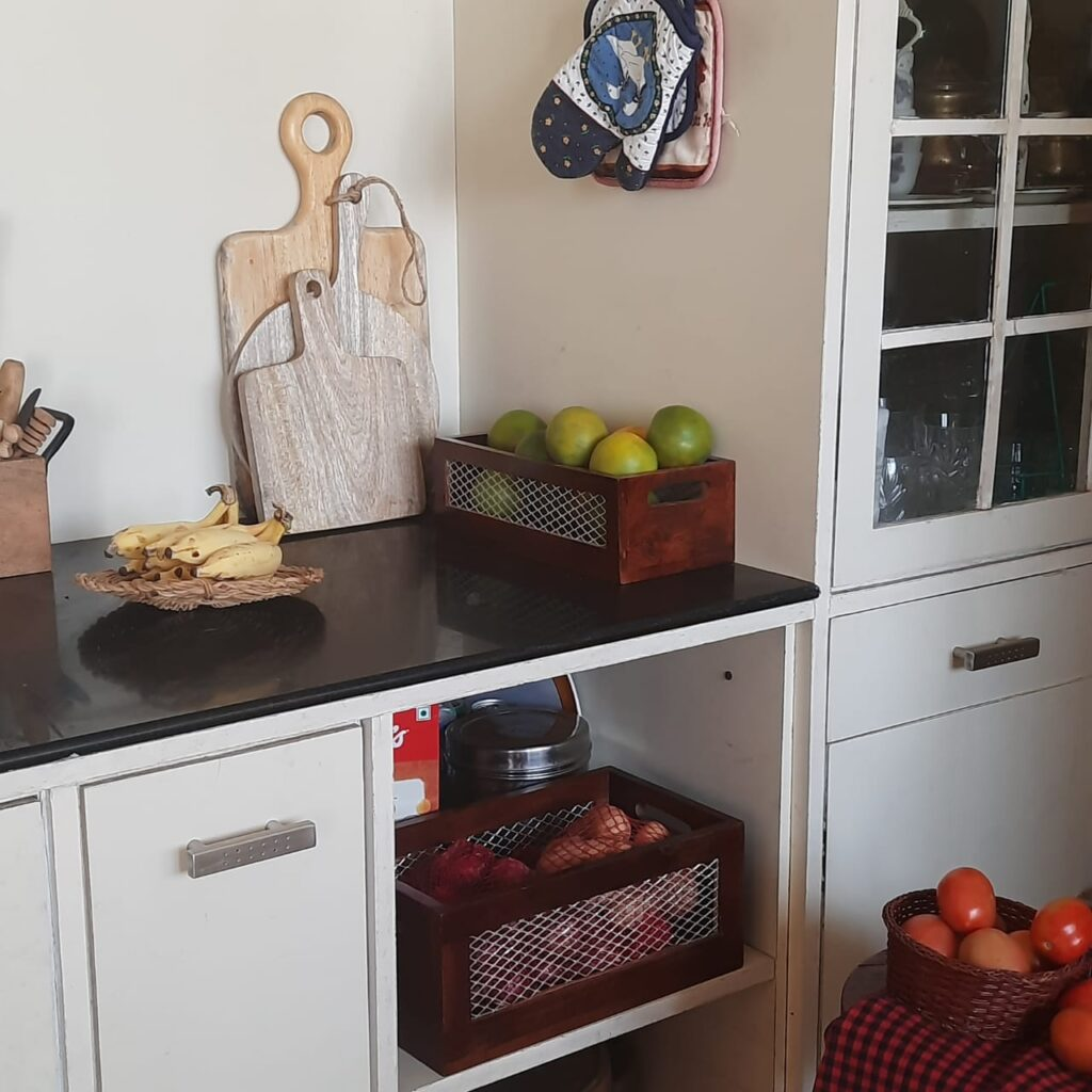 The kitchen filled with a flat woven plate to hold the bananas, a round dark cane basket to hold the tomatoes, propped on the stool, chopping or cheese boards, and of course the baskets of produce | A case for Baskets | TheKeybunch decor blog