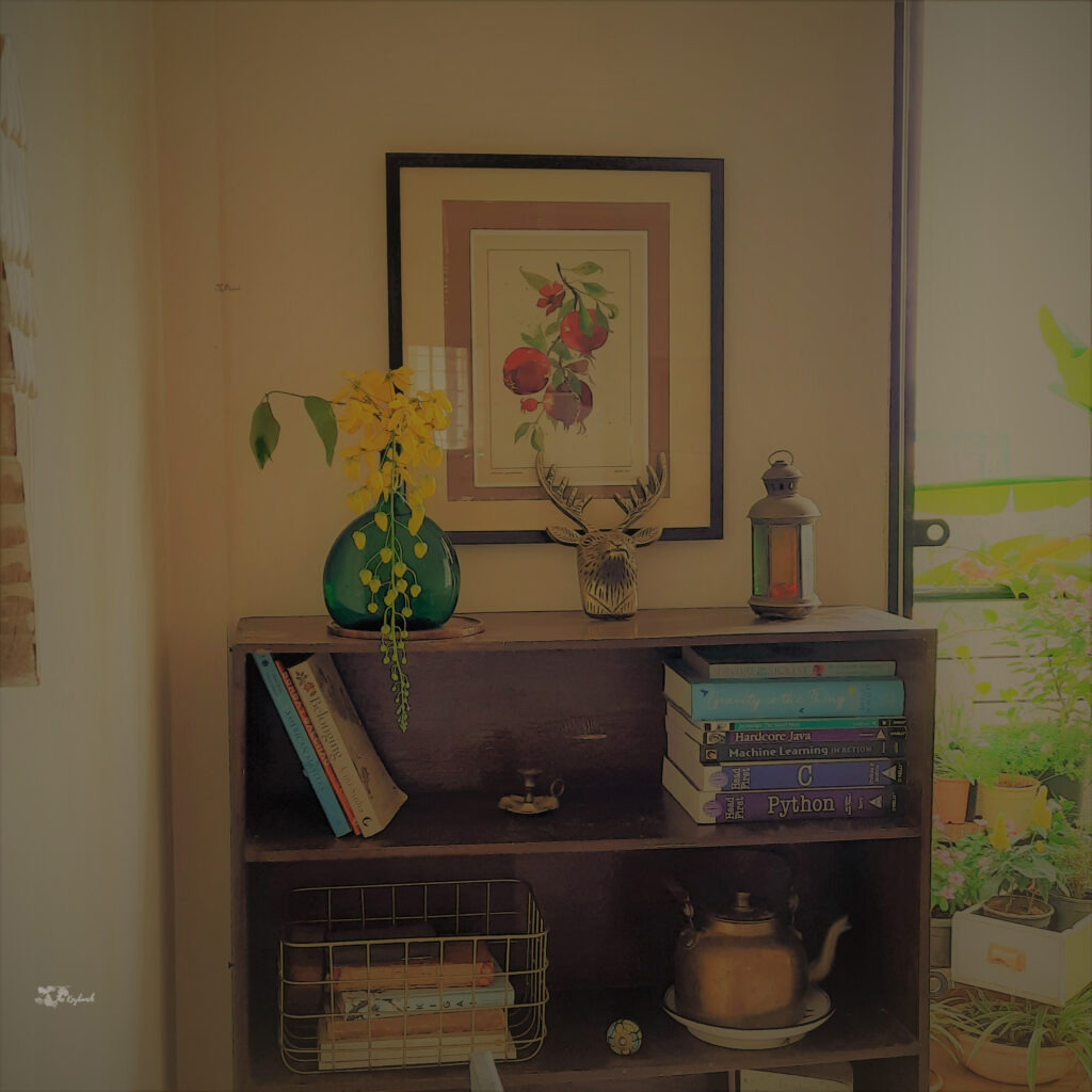 Decorate with a touch of yellow during the pandemic | Yellow flowers, frame, animal skull, collection of books, brass candle stand, kettle brass at wooden shelves at the corner of the living room