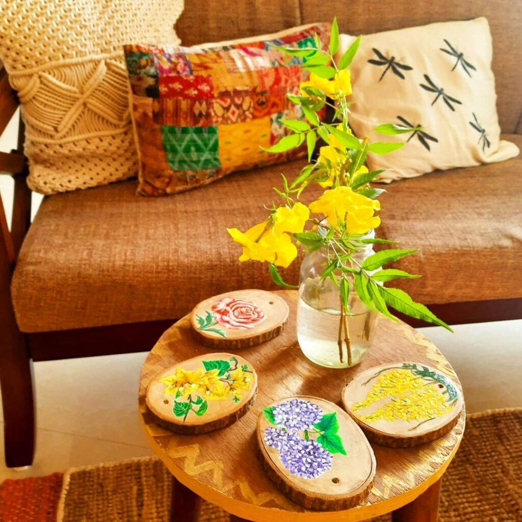 Decorate with a touch of yellow during the pandemic | A colourful cushion cover with some small patches of yellow, along with coasters painted with yellow flowers