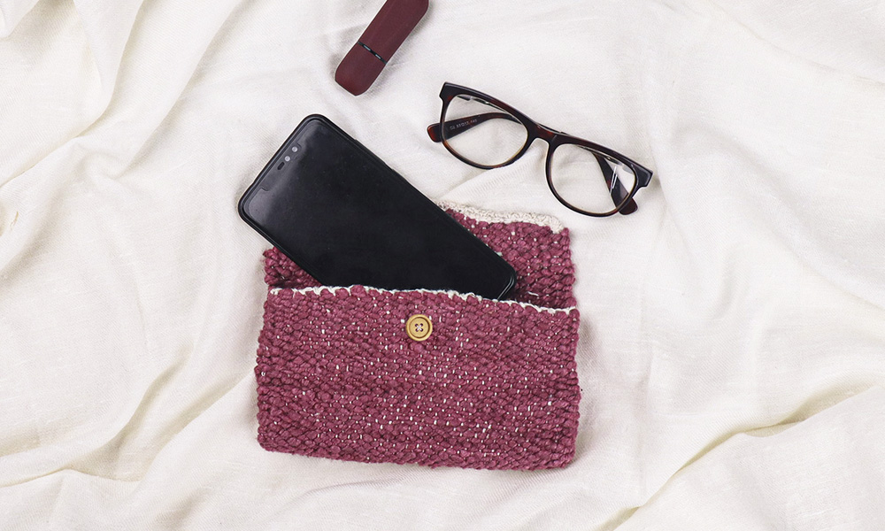 a hand clutch with a mobile fitting in, and spectacles close by | 6 Tapestry DIYs on Muezart's home-use loom