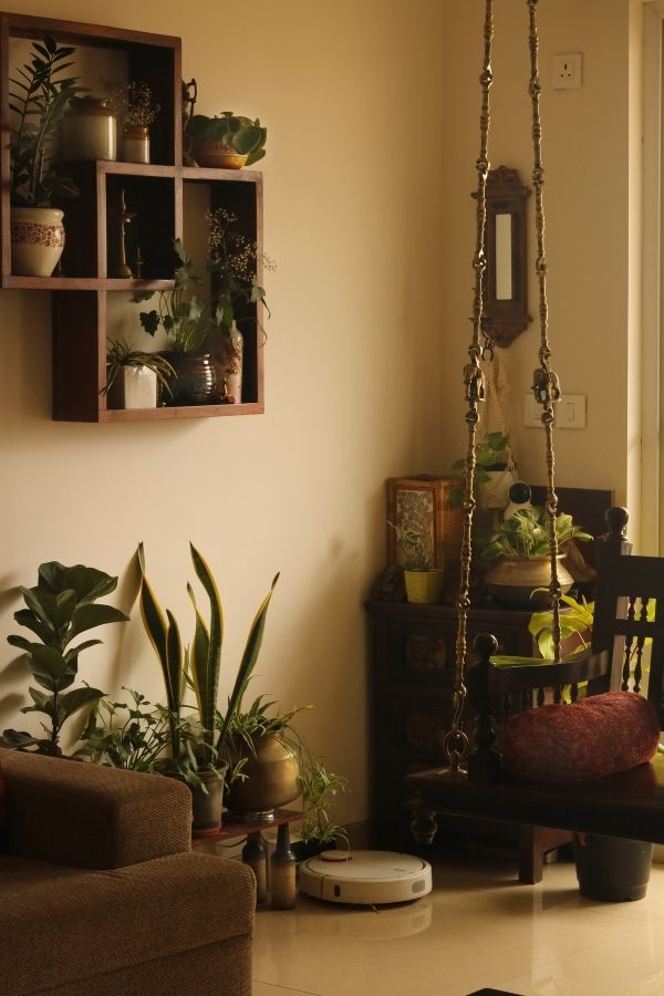 A jhoola swing, green house plants and brass planters are decorated in living room | Home Tour: A beautiful Antique Modern home in Bangalore