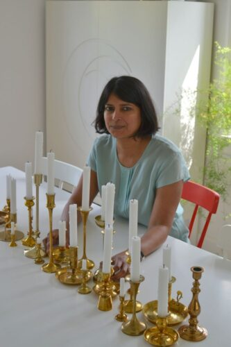 The beautiful shot of Naina with a collection of brass candle stand holder on the dining table | Naina's Scandi-Indian minimal home