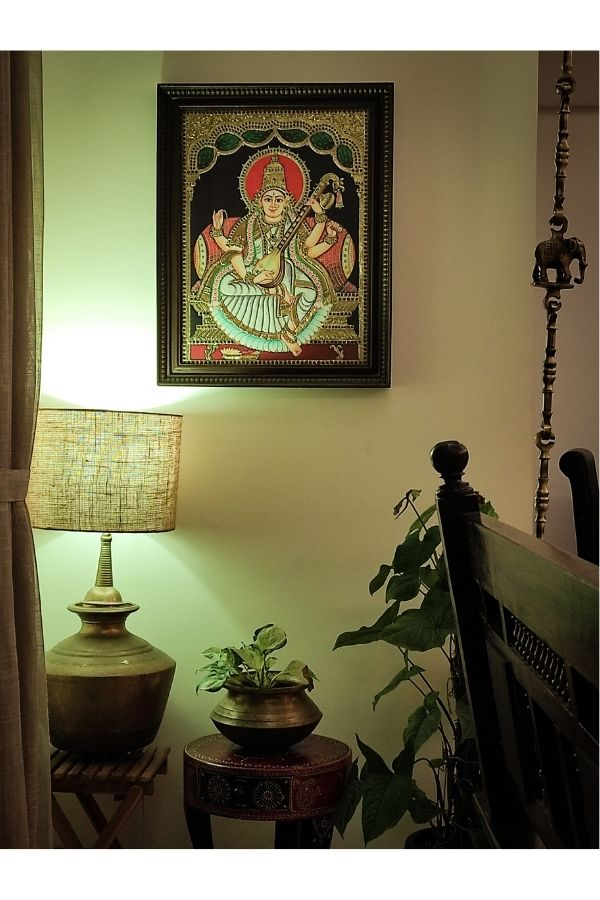 The tanjore paintings, brass table lamp, brass vase and green plants at the corner of the living room | Home Tour: A beautiful Antique Modern home in Bangalore
