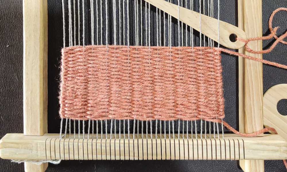 A closeup of a home loom, with orange eri silk thread forming an unfinished tapestry | 6 Tapestry DIYs on Muezart's home-use loom