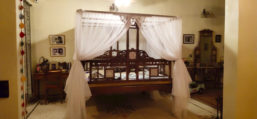Villa Rashmi - A Heritage Gem in Mumbai   The bedroom was decorated with family frame, wooden dresser and wooden reading desk at the corner of the room   TheKeybunch decor blog