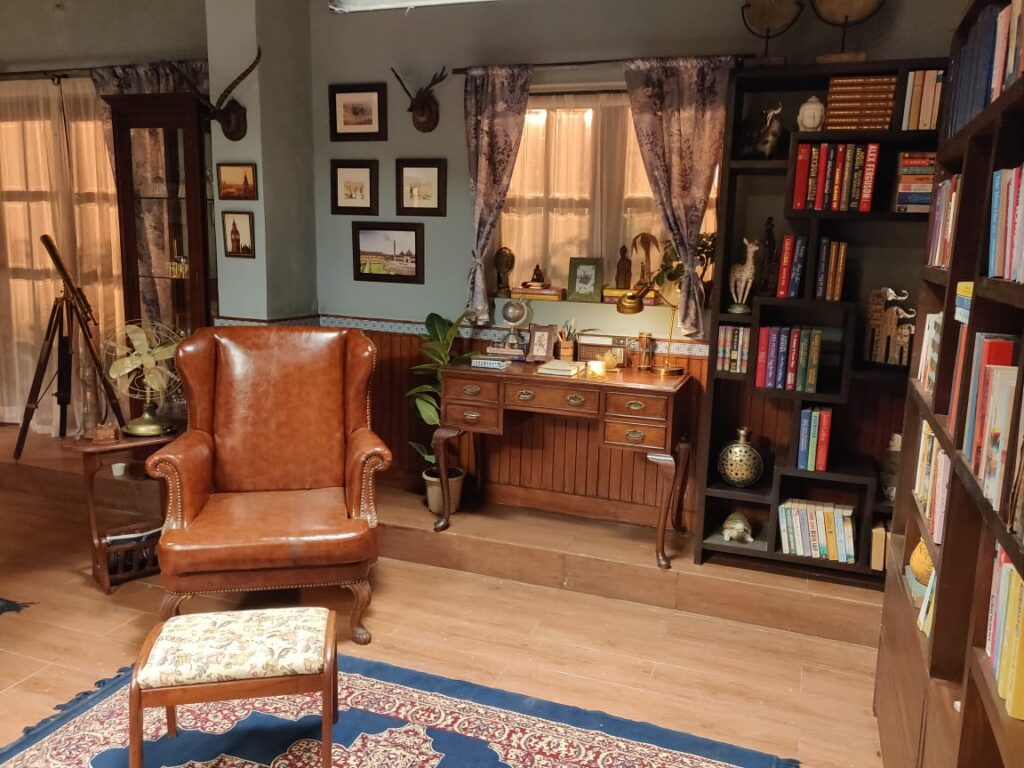Villa Rashmi - A Heritage Gem in Mumbai   Wing chair, vintage books on wooden shelf and console table at the reading room   TheKeybunch decor blog
