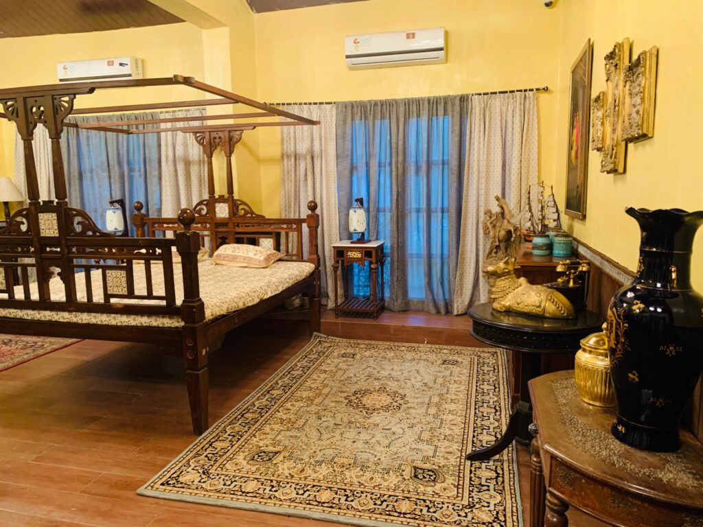 Villa Rashmi - A Heritage Gem in Mumbai   Traditional Indian bed with lamp on side table, wall frames and vintages decorated at the bedroom   TheKeybunch decor blog