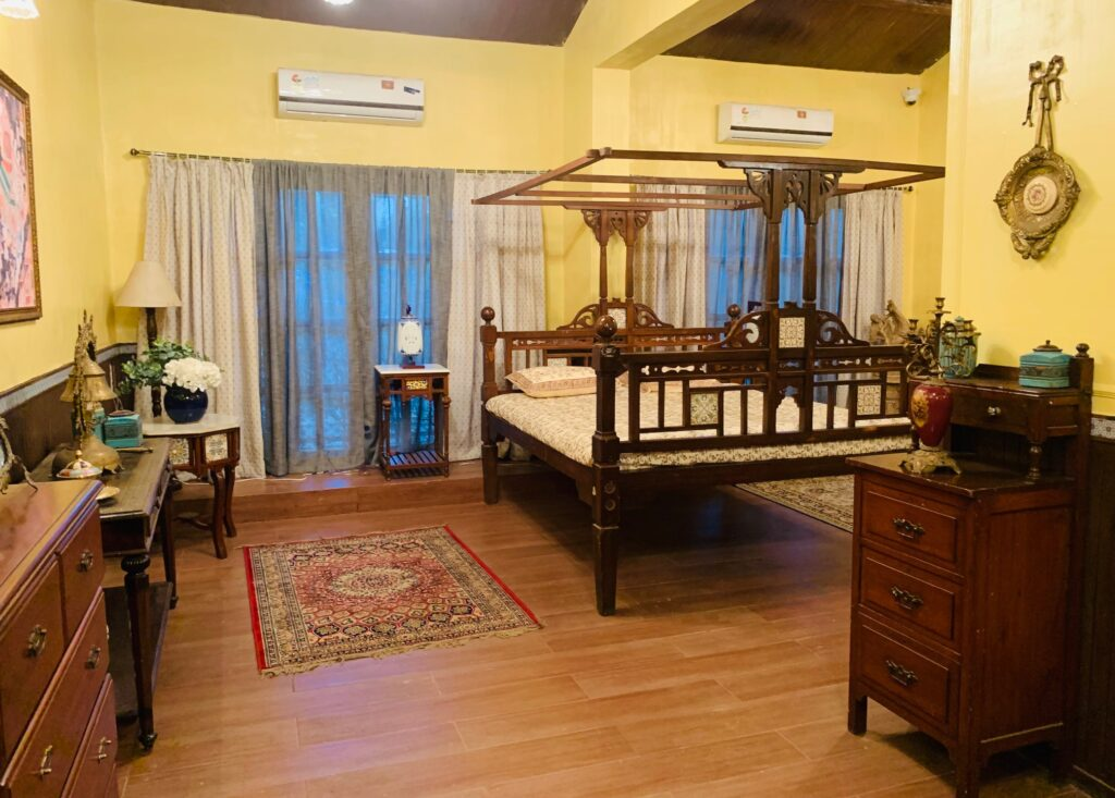 Villa Rashmi - A Heritage Gem in Mumbai   Traditional Indian bed with lamp on side table, wall frames, wooden table and vintages decorated at the bedroom   TheKeybunch decor blog