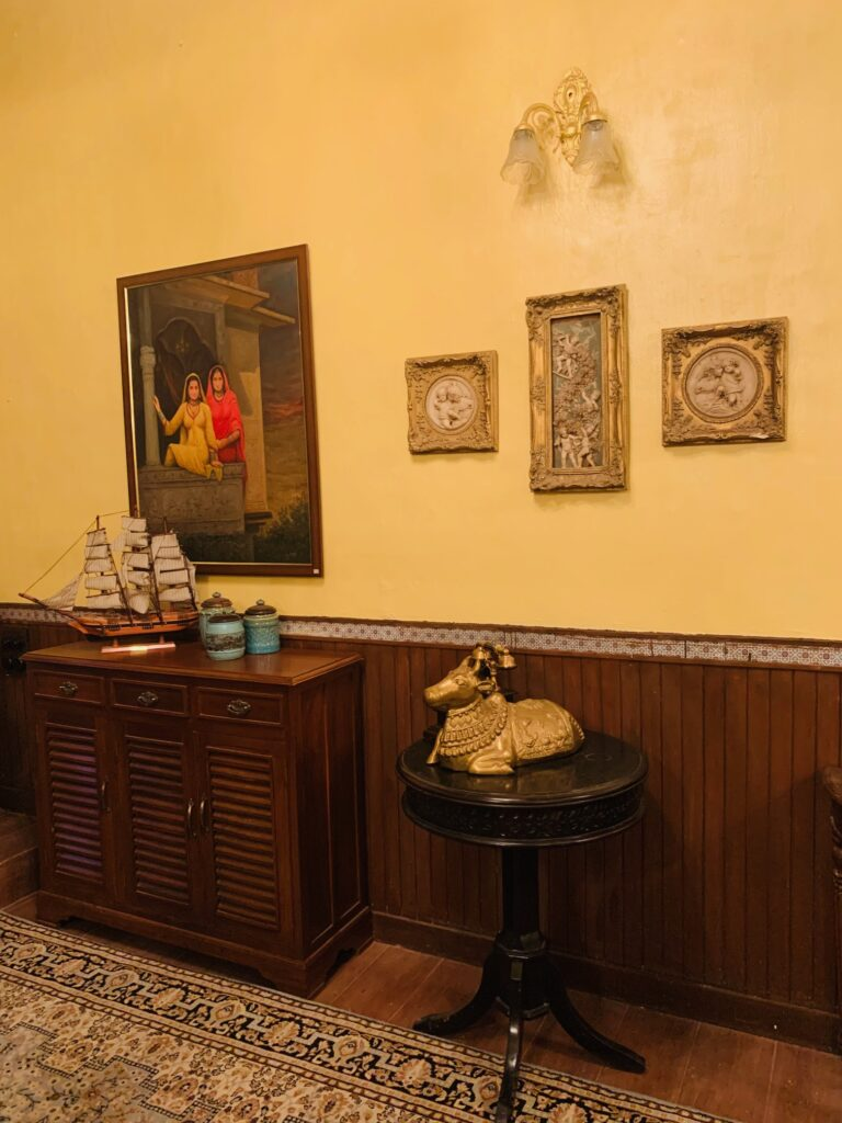Villa Rashmi - A Heritage Gem in Mumbai   The bedroom corner was decorated with wall frames, vintages on top of wooden cabinet and brass nandi statue on top of the table   TheKeybunch decor blog