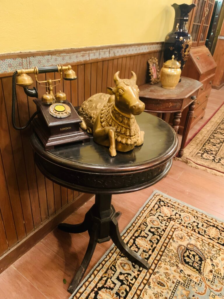Villa Rashmi - A Heritage Gem in Mumbai   Brass nandi statue, wooden brass antique telephone and brass jar box are on top of the table at the corner of the bedroom   TheKeybunch decor blog