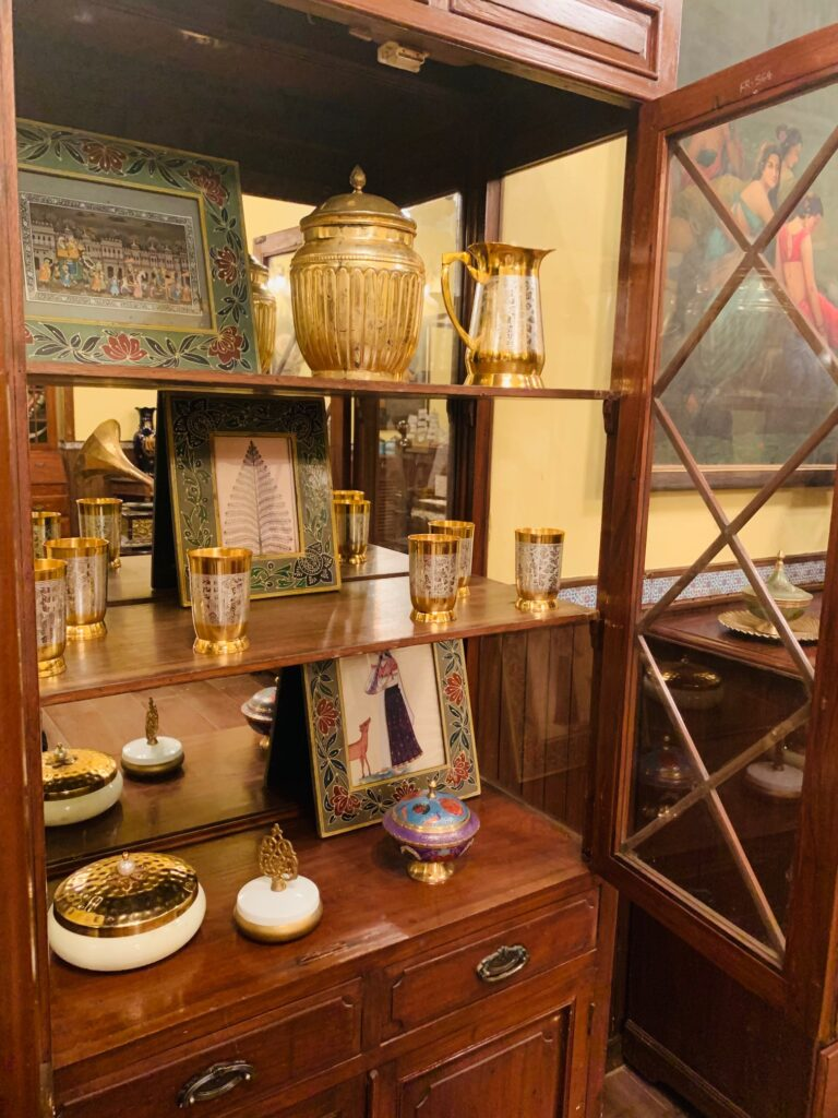 Villa Rashmi - A Heritage Gem in Mumbai   The brass collection and frames at glass display cabinet in the bedroom   TheKeybunch decor blog