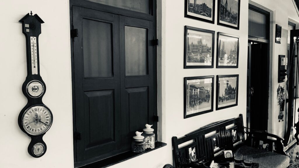 Villa Rashmi - A Heritage Gem in Mumbai   Old antique clock with wall frames in black and white colors   TheKeybunch decor blog