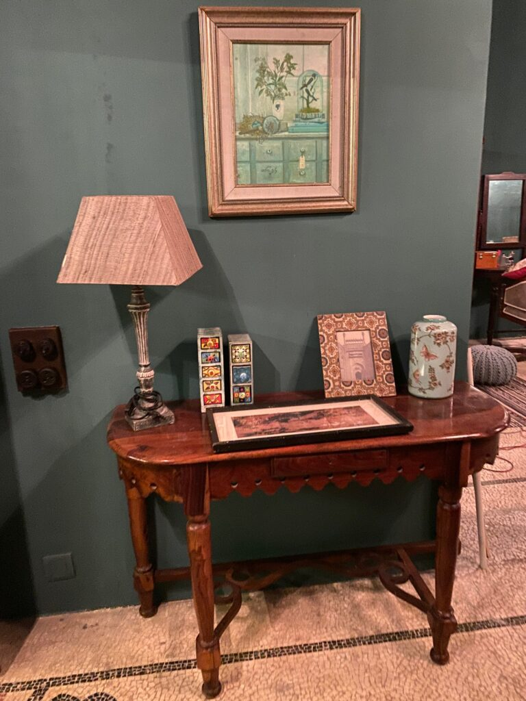 Villa Rashmi - A Heritage Gem in Mumbai   Table lamp and frames on top of the table at the corner of the room   TheKeybunch decor blog