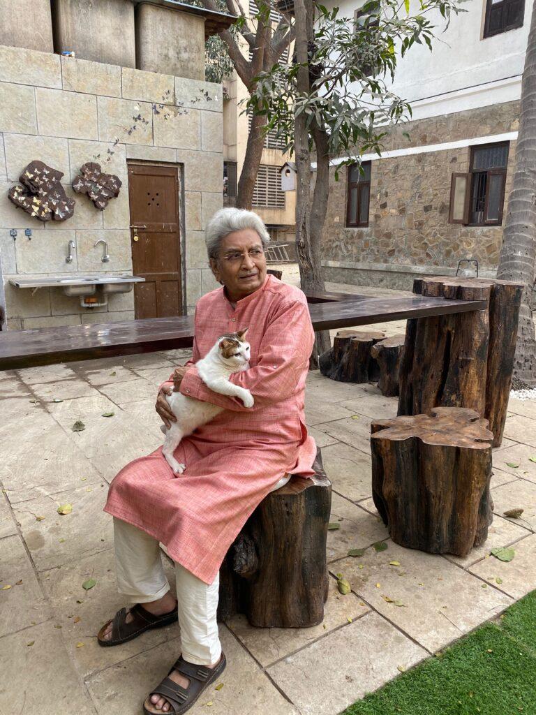 Villa Rashmi - A Heritage Gem in Mumbai   Haresh Patel sitting on wooden tree stump stool at the backyard of the villa   TheKeybunch decor blog
