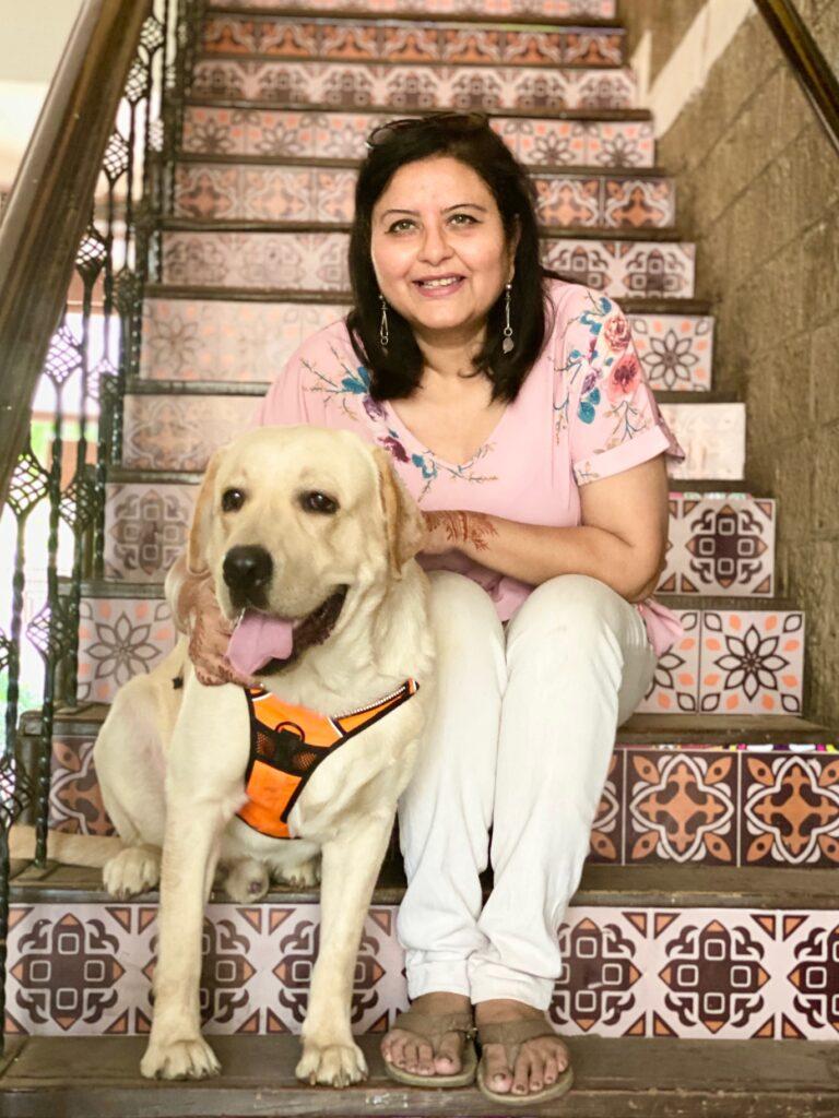 Villa Rashmi - A Heritage Gem in Mumbai   Deval Patel with her dog sitting on stair   TheKeybunch decor blog