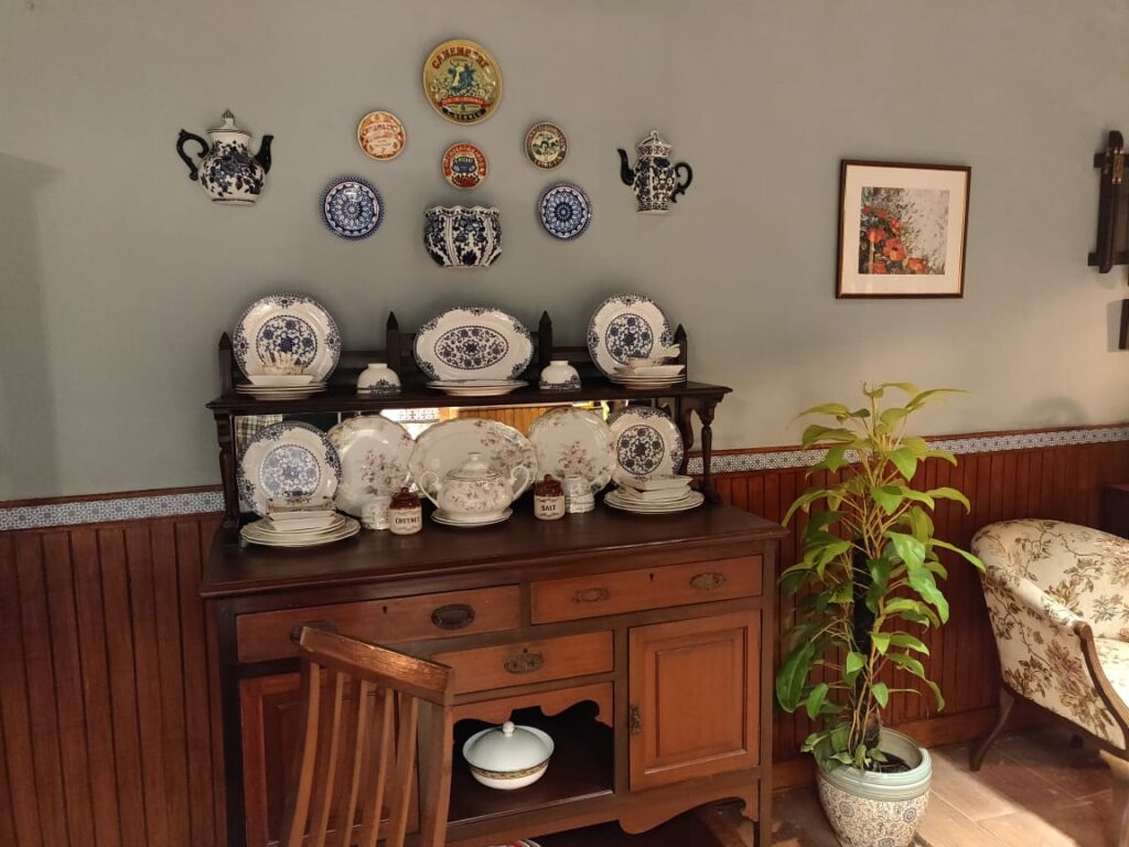 Villa Rashmi - A Heritage Gem in Mumbai   The living room wall was decorated with wall plate and wall mounted kettle, and the ceramic plates on top of wooden cabinet   TheKeybunch decor blog