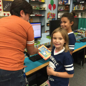 Two students receive help checking out books from the Summitt Library