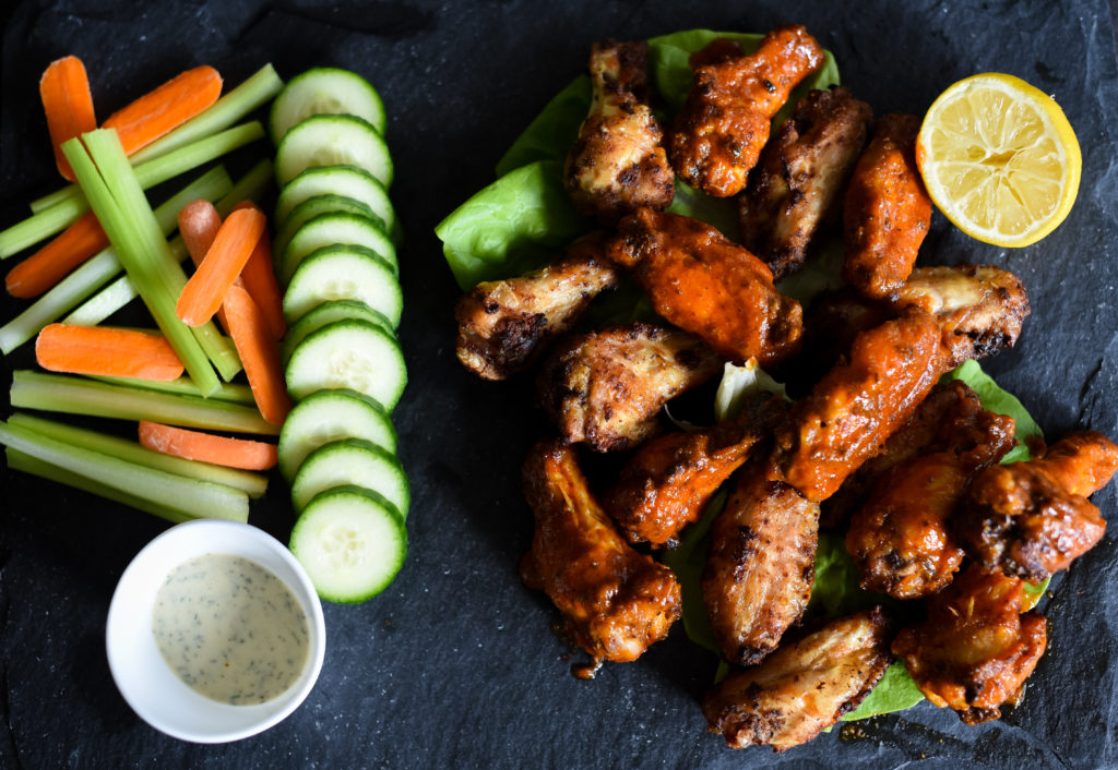 Traditional hot wings with a little zing! Crispy Lemon Pepper hot wings seasoned with lemon garlic seasoning, tossed with a traditional buffalo wing sauce served with a squeeze of lemon juice.